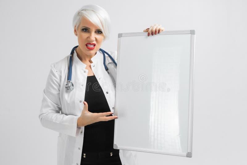Kvinna i en vit ämbetsdräkt med ett magnetiskt bräde i hennes händer ett ställe för en etikett arkivfoton