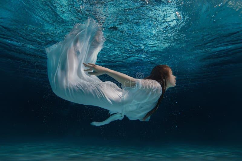 Kvinna i en vit klänning under vatten royaltyfria foton