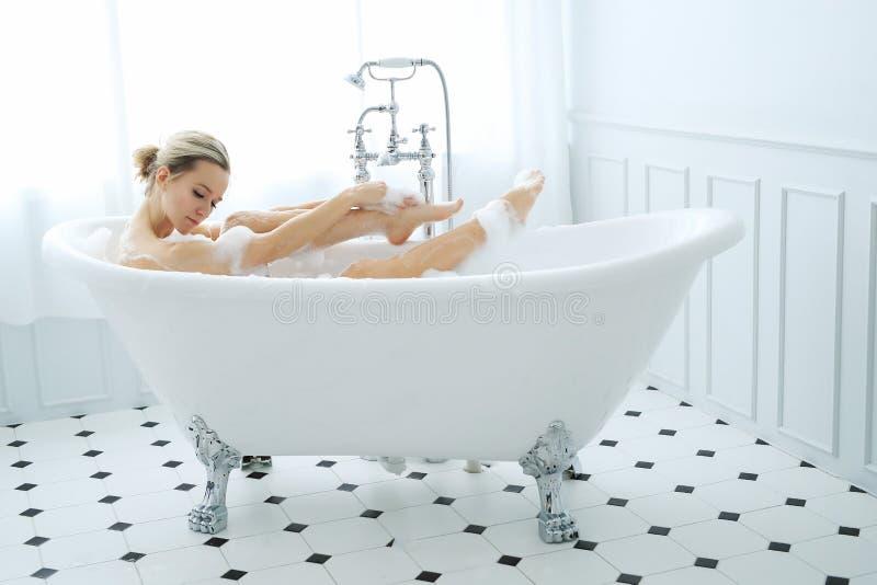Kvinna i ett badkar arkivfoto