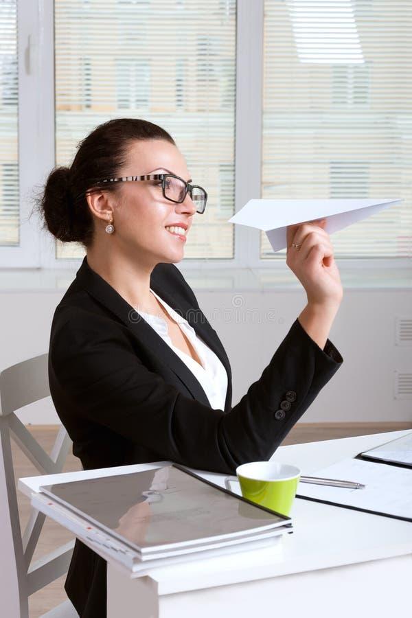 Kvinna i ett dräktsammanträde på tabellen i regeringsställning som kastar pappers- airpla royaltyfria bilder