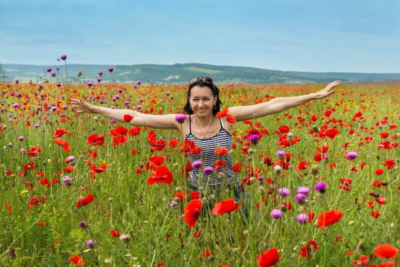 Kvinna i ett fält av den blommande vallmo royaltyfria bilder