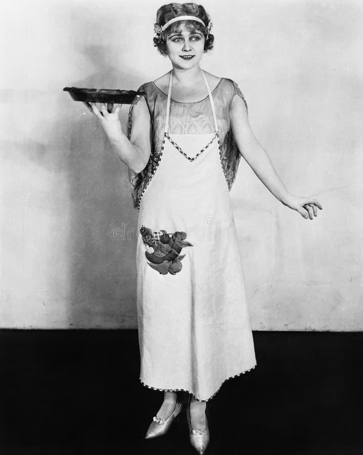 Kvinna i ett förkläde som rymmer en platta av mat och le (alla visade personer inte är längre uppehälle, och inget gods finns lev fotografering för bildbyråer