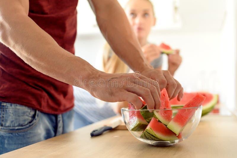 kvinna i ett kök som äter den röda vattenmelon och ser hennes make, par i deras stora moderna vita kök fotografering för bildbyråer