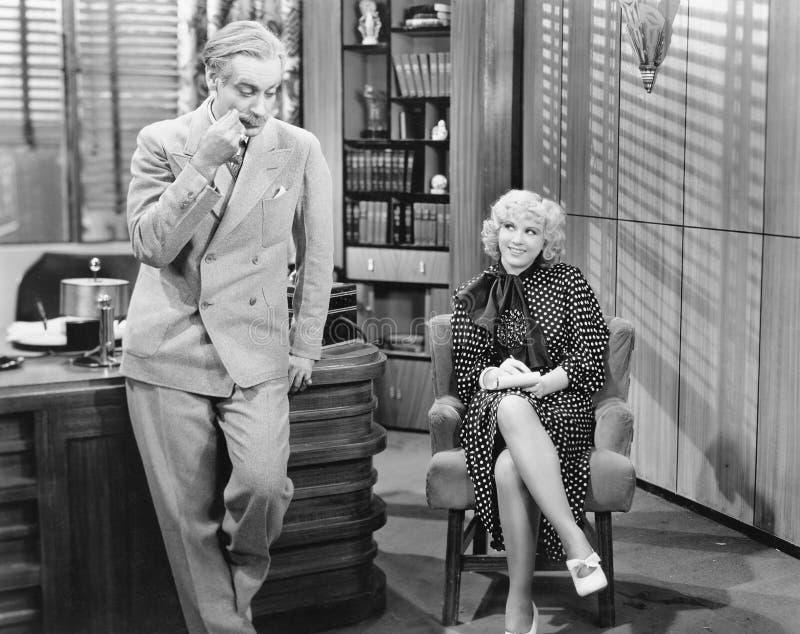 Kvinna i ett kontor som tar diktamen och flörtar med mannen (alla visade personer inte är längre uppehälle, och inget gods finns  arkivbild