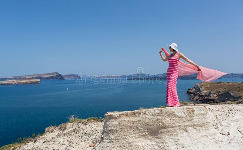 Kvinna i ett långt sommarklänninganseende på en klippa royaltyfri bild