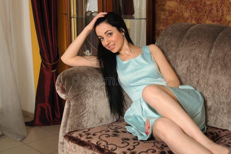 Kvinna i ett turkosklänningsammanträde på en soffa arkivfoto