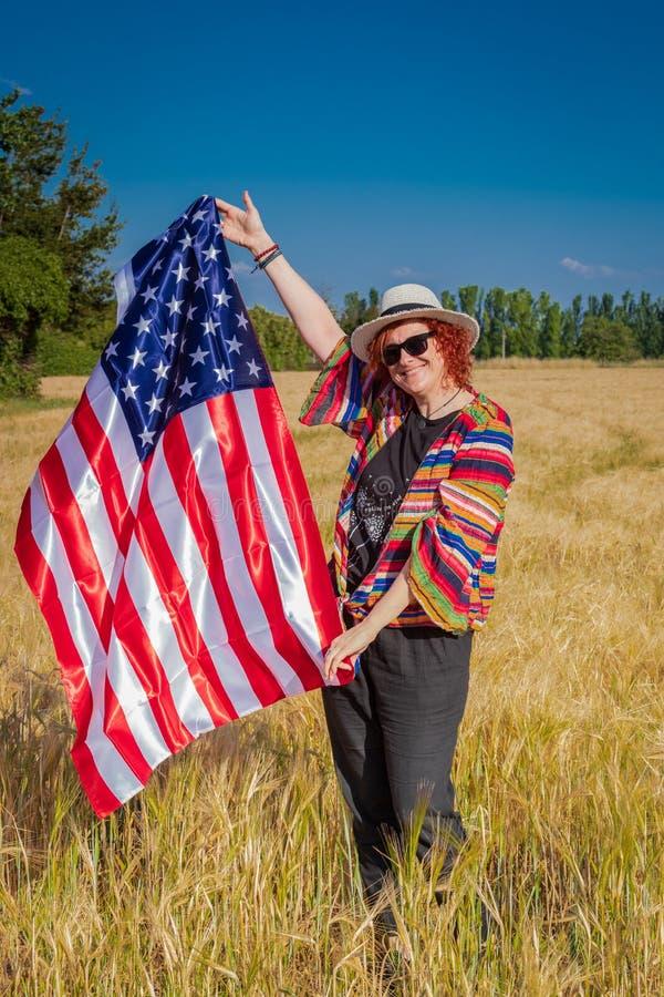 Kvinna i ett vetefält med en USA flagga arkivbild