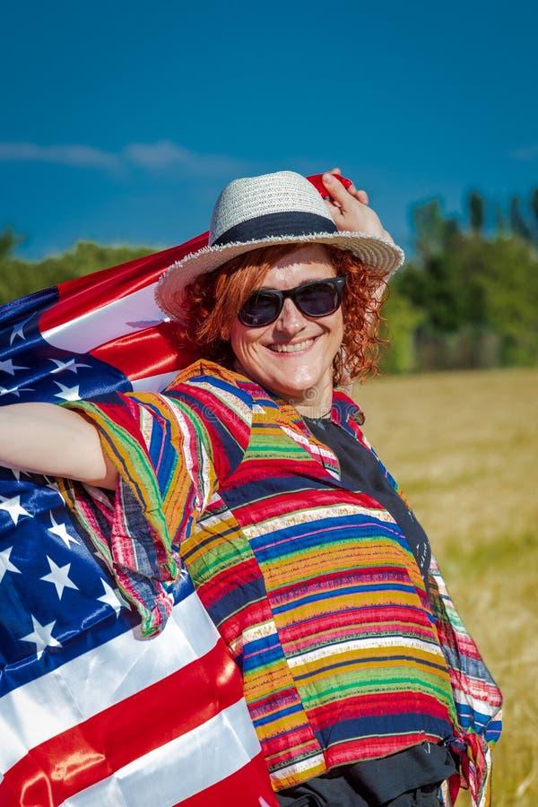 Kvinna i ett vetefält med en USA flagga royaltyfria foton