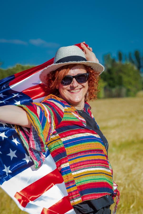 Kvinna i ett vetefält med en USA flagga royaltyfria bilder