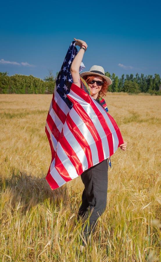Kvinna i ett vetefält med en USA flagga royaltyfri bild