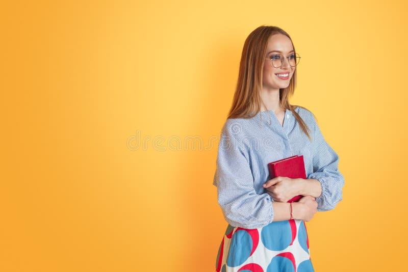 Kvinna i exponeringsglas med boken i studio royaltyfria bilder
