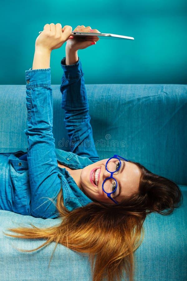 Kvinna i exponeringsglas som lägger på soffan med PCminnestavlan royaltyfria foton