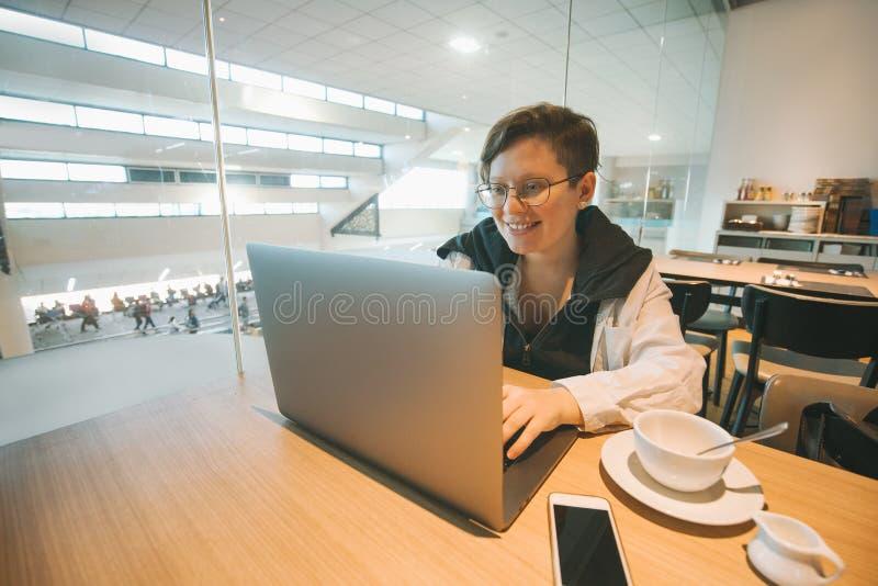 Kvinna i exponeringsglasarbete på bärbara datorn till flygplatsen Grejer internet, bloggers arkivbild