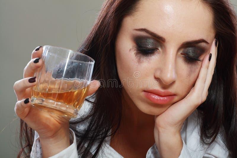 Kvinna i fördjupning som dricker alkohol arkivfoton