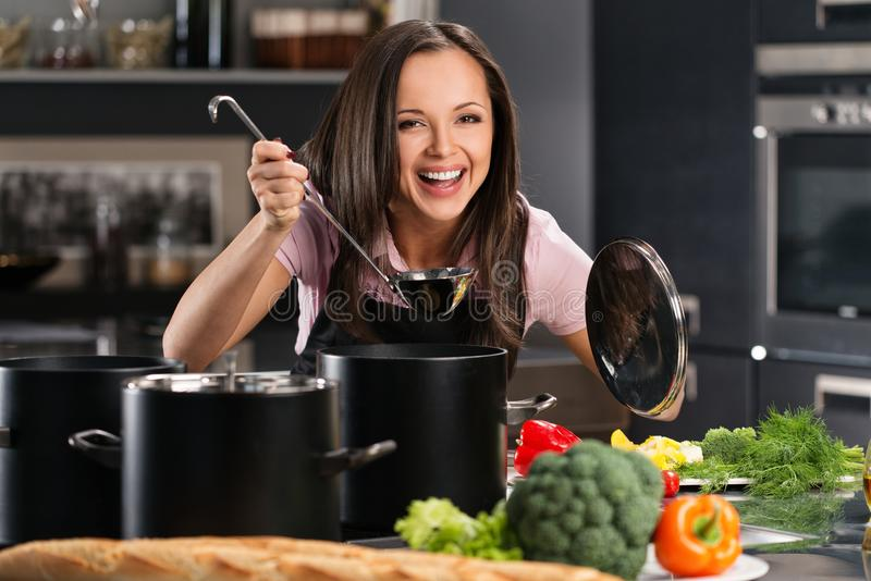 Kvinna i förkläde på modernt kök royaltyfri fotografi