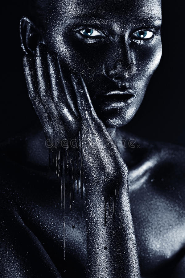 Kvinna i flödande rörande framsida för svart målarfärg fotografering för bildbyråer