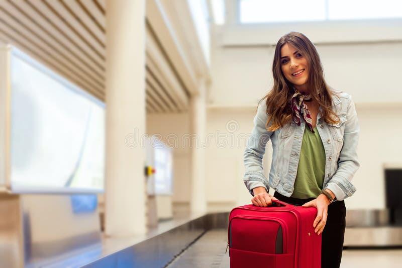 Kvinna i flygplatsen som samlar hennes bagage på transportbandområde arkivfoto