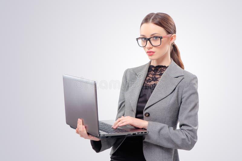 Kvinna i formalwearen som arbetar på bärbara datorn royaltyfri bild