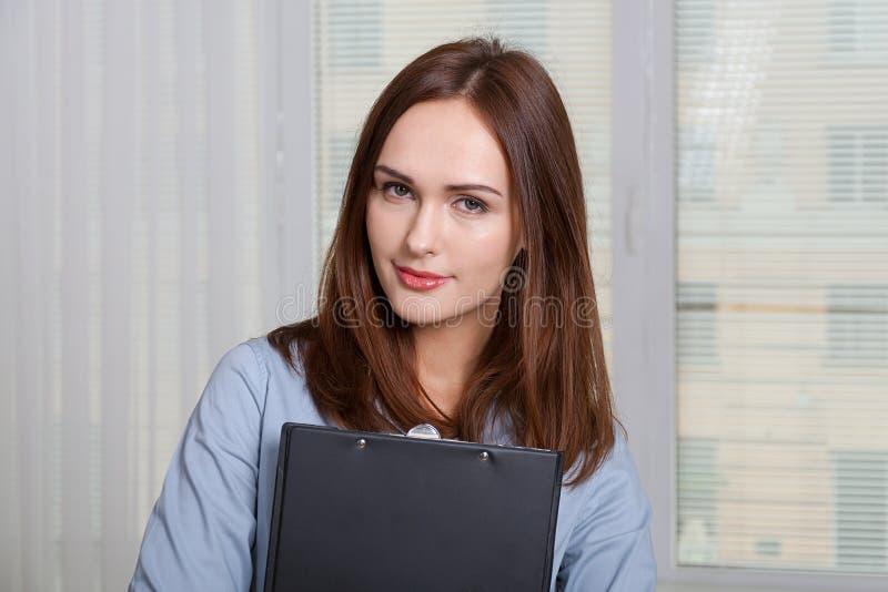 Kvinna i formell dress som rymmer en mapp royaltyfria bilder