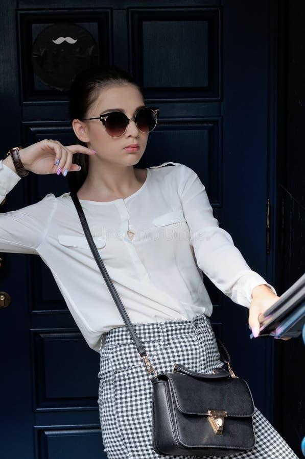 Kvinna i formell kläder som står nära dörren fotografering för bildbyråer