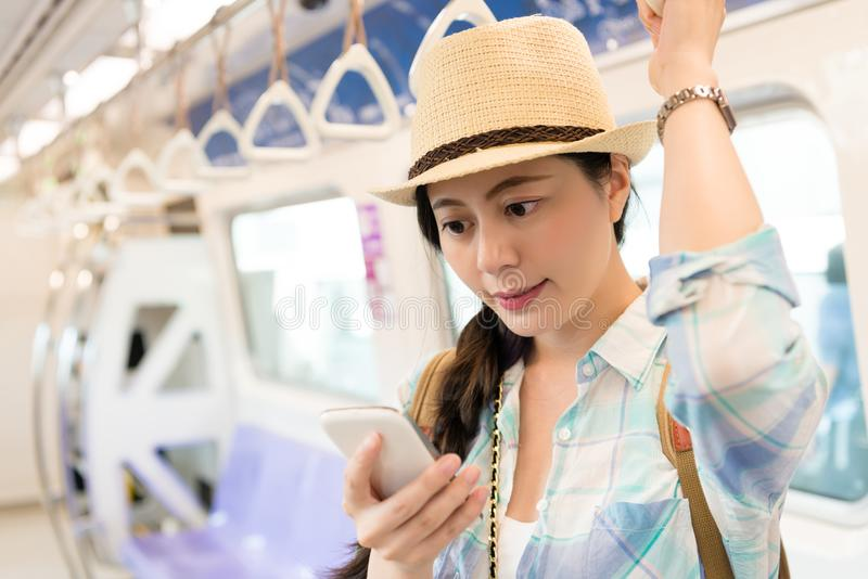 Kvinna i gångtunnelen genom att använda smartphonen fotografering för bildbyråer
