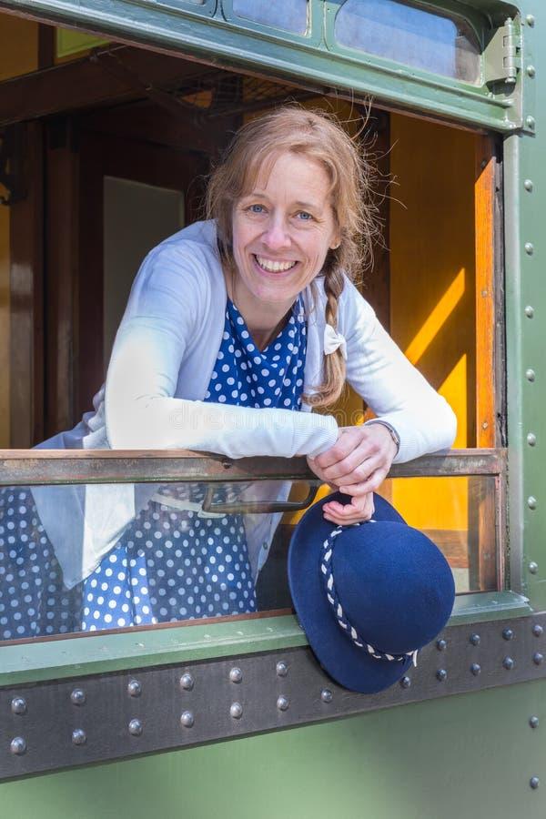 Kvinna i gammalmodig kläder som rymmer hatten i drevfönster royaltyfria bilder