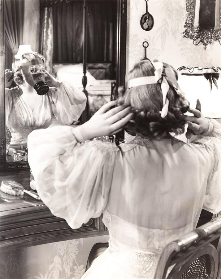 Kvinna i gasmasken som ser i spegel arkivfoton
