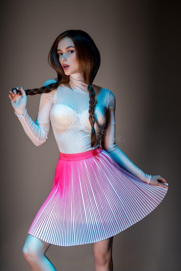 Kvinna i genomskinlig blus och rosa färgkjol arkivfoton