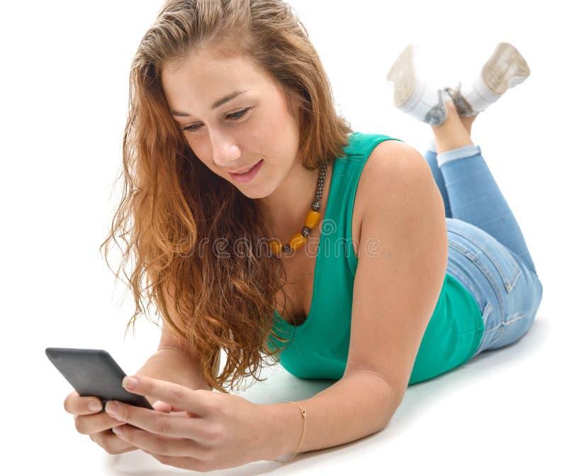 Kvinna i gröna tillfälliga kläder som ligger golvet, hållande smartph royaltyfri foto