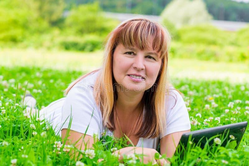 Kvinna i grönt gräs med blommor royaltyfri bild
