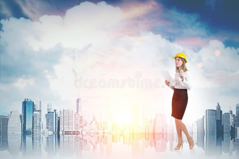 Kvinna i gul hård hatt och cityscape royaltyfria bilder