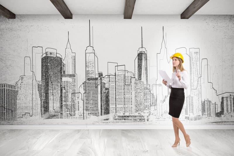 Kvinna i gul hård hatt och cityscape på betongväggen fotografering för bildbyråer
