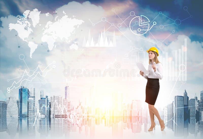 Kvinna i gul hård hatt och diagram mot cityscape fotografering för bildbyråer