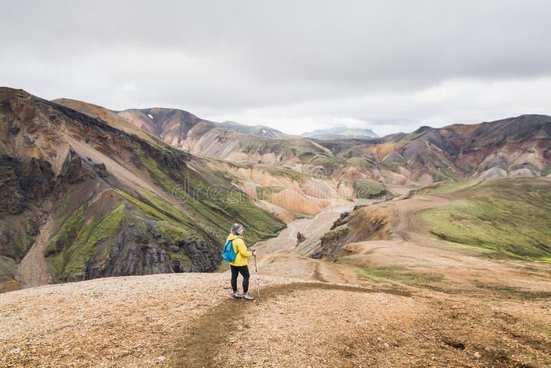 Kvinna i gul regnrock som fotvandrar i de färgglade bergen i den Landmannalaugar nationalparken, Island fotografering för bildbyråer