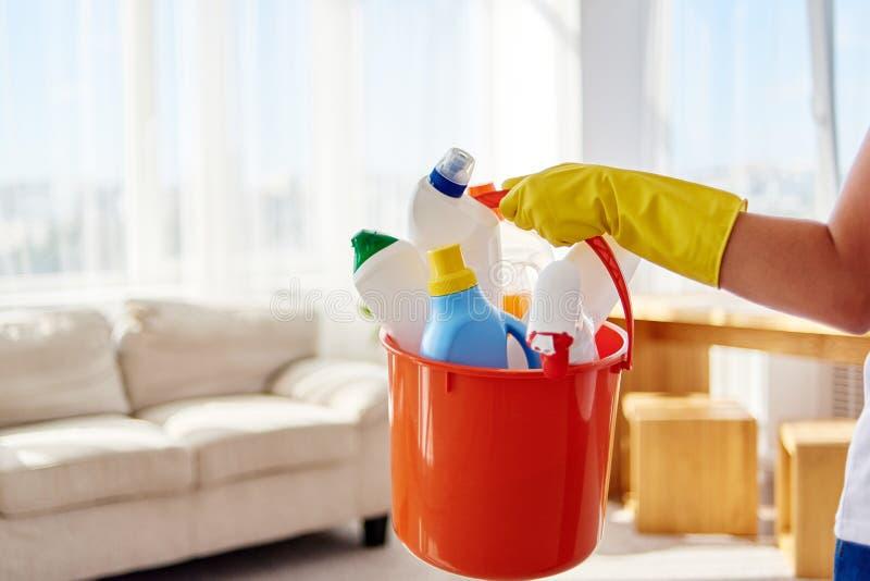 Kvinna i gula gummihandskar som hemma rymmer i handlokalvårdprodukter i orange hink i vardagsrum, kopieringsutrymme hush?llsarbet arkivbilder