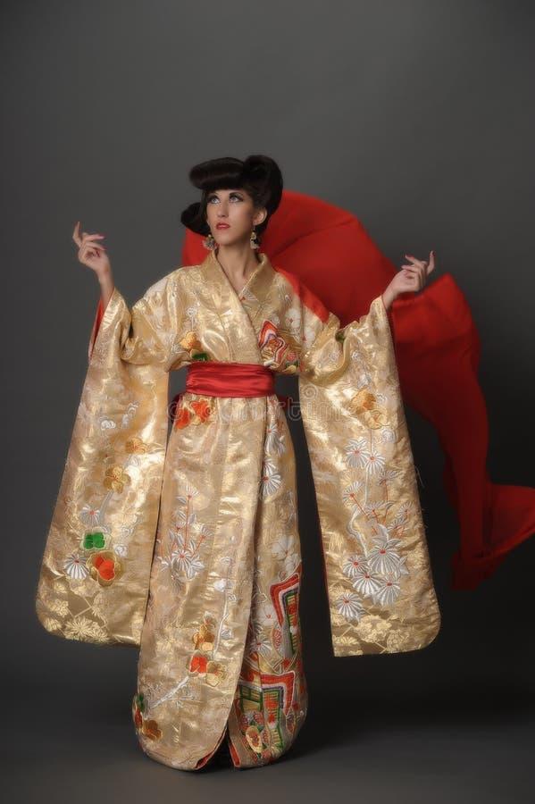 Kvinna i guld- kimano fotografering för bildbyråer