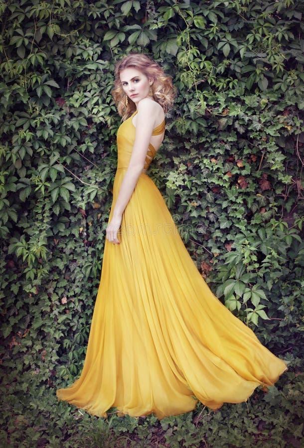 Kvinna i guld- klänning, i natur arkivfoton