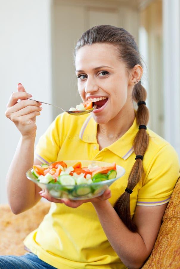 Kvinna som äter grönsaksallad på sofaen arkivfoto