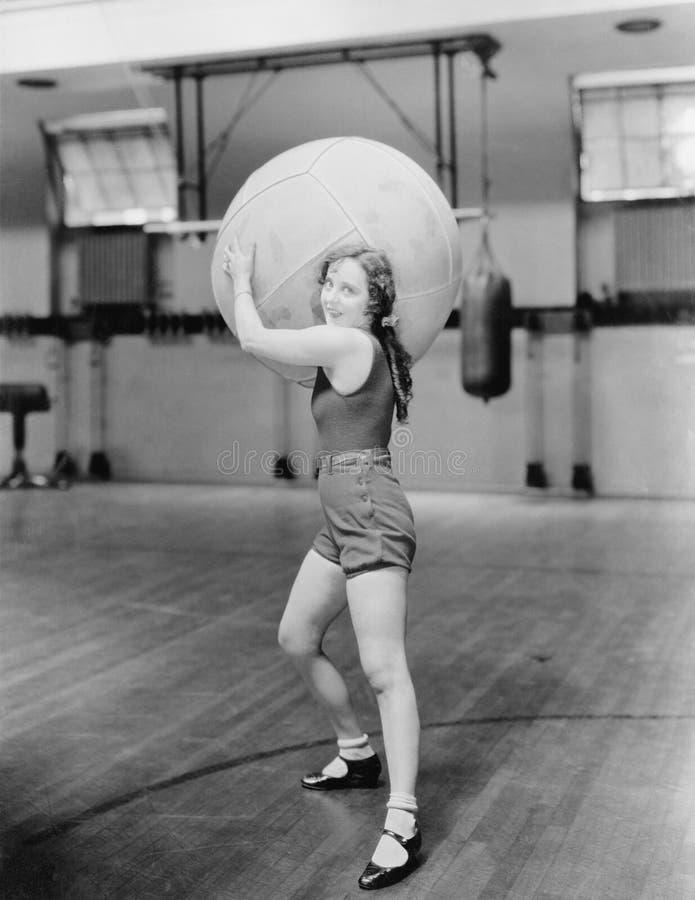 Kvinna i gymnastiksal med den enorma bollen (alla visade personer inte är längre uppehälle, och inget gods finns Leverantörgarant royaltyfri fotografi