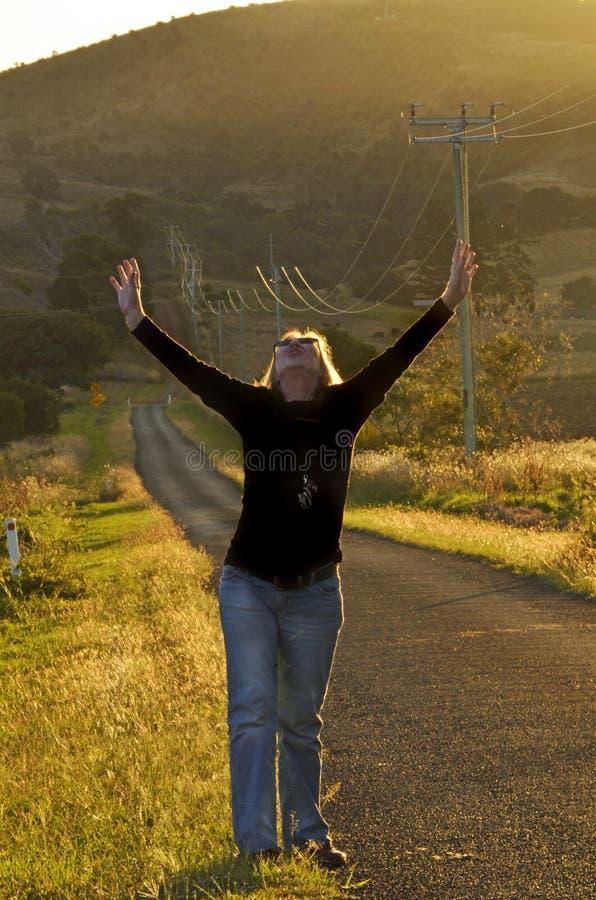Kvinna i härlig bygd som lyfter armar för att tacka guden för svarad bön arkivbild