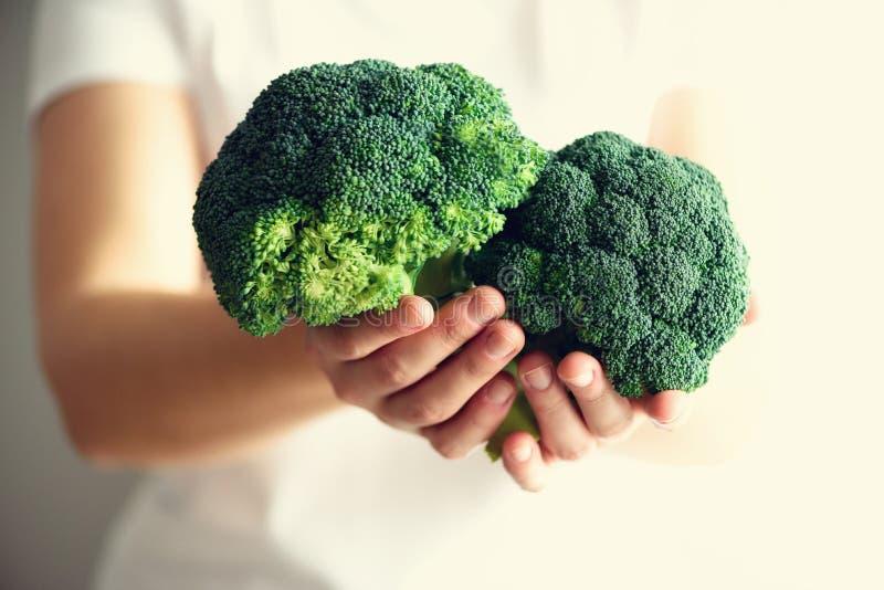 Kvinna i hållande broccoli för vit T-tröja i händer kopiera avstånd Sund ren detox som äter begrepp Vegetarian strikt vegetarian  arkivbild