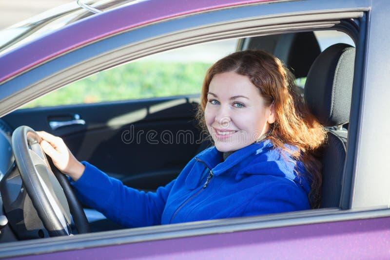 Kvinna i hållande styrninghjul för bil fotografering för bildbyråer