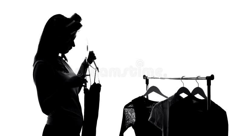 Kvinna i hårrullar som väljer klänningen som förbereder sig för möte, modekläder royaltyfria foton