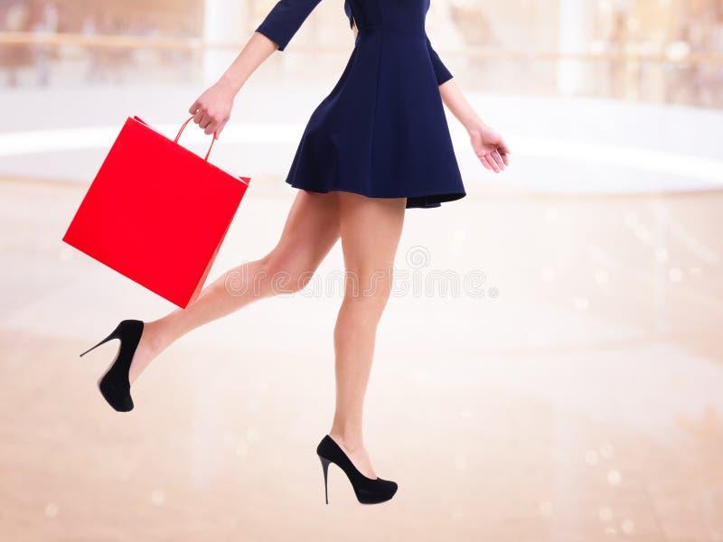 Kvinna i höga häl med den röda shoppingpåsen.