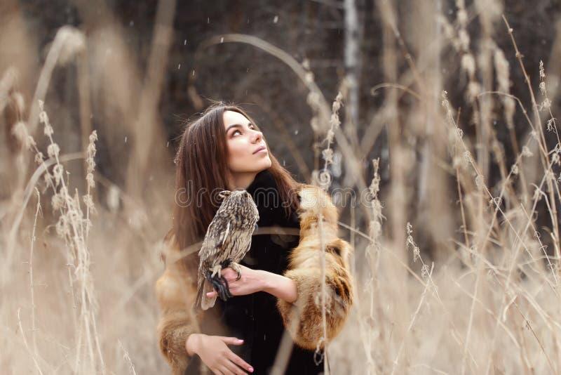 Kvinna i höst i pälslag med snö för uggla förestående först Härlig brunettflicka med långt hår i naturen som rymmer en uggla arkivbild