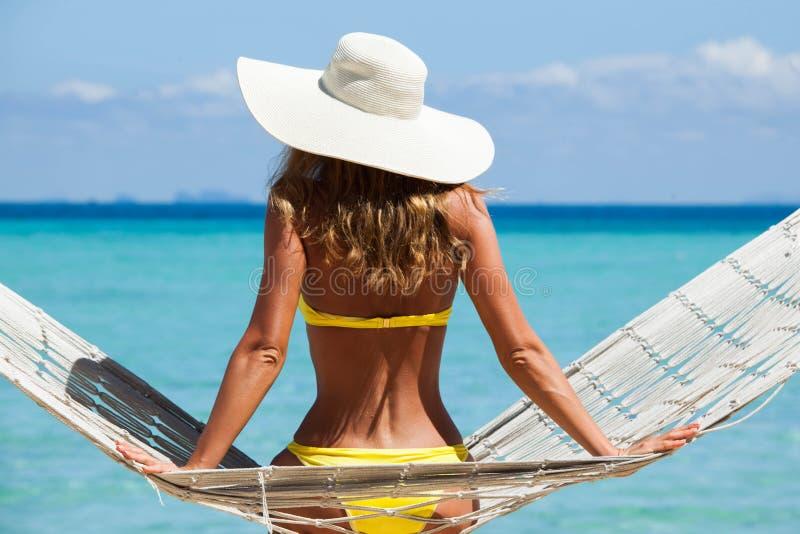 Kvinna i h?ngmatta p? strand royaltyfri foto