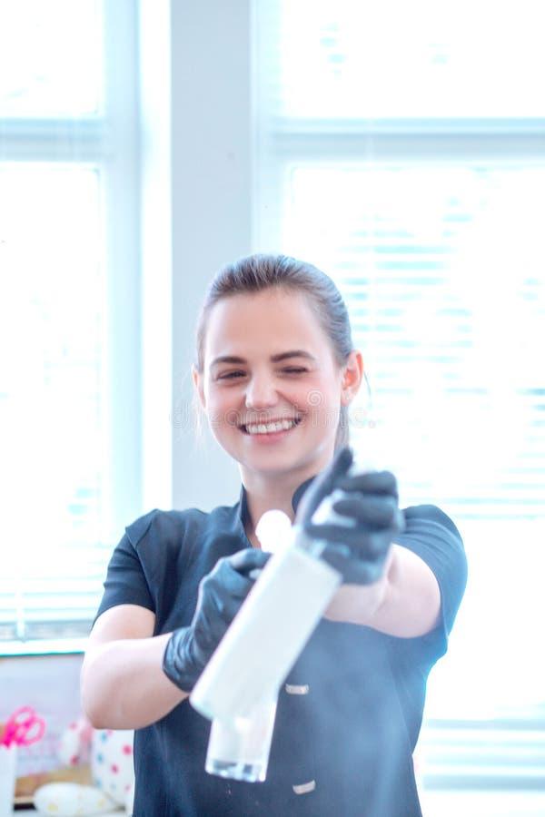 Kvinna i handskar och med antibacterial sprej arkivbild