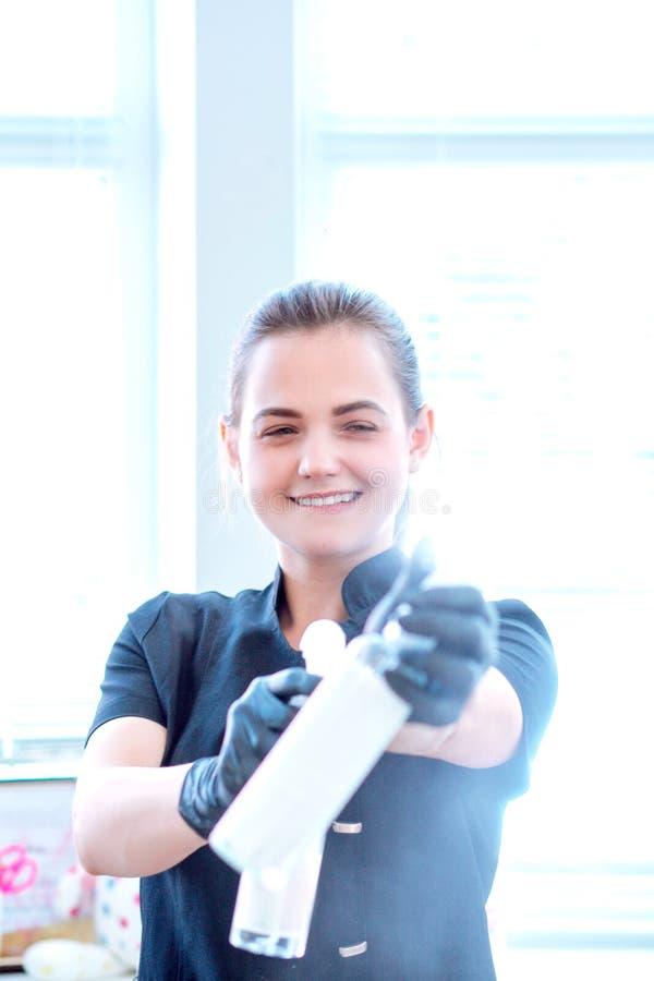 Kvinna i handskar och med antibacterial sprej royaltyfria foton