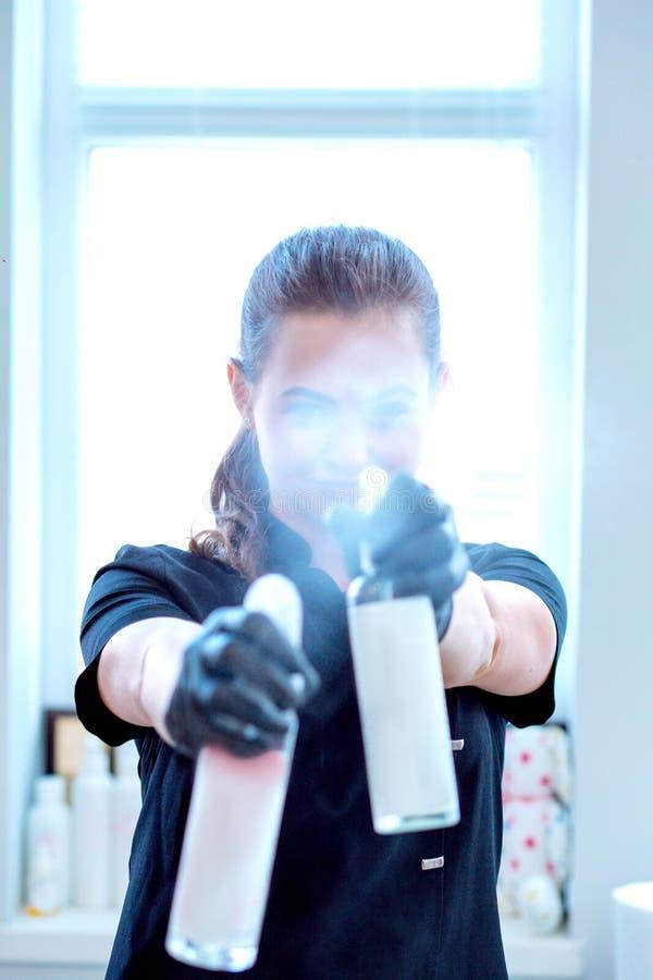 Kvinna i handskar och med antibacterial sprej arkivfoton