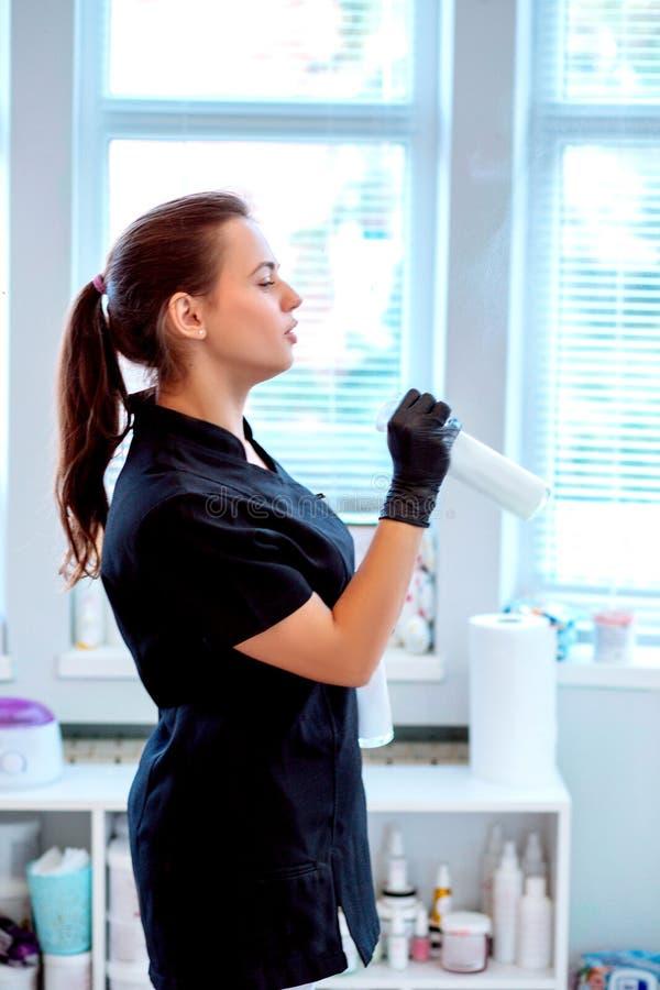 Kvinna i handskar och med antibacterial sprej arkivbilder